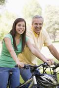 Man and girl on bikes outdoors smiling - stock photo