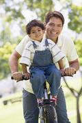 Man and young boy on a bike outdoors smiling Stock Photos