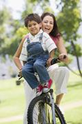 Woman and young boy on a bike outdoors smiling - stock photo