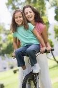 Woman and young girl on a bike outdoors smiling Stock Photos