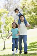 Man with two young children running outdoors smiling Stock Photos