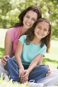 Woman and young girl sitting outdoors smiling - stock photo