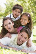 Family lying outdoors smiling - stock photo