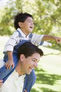 Man giving young boy shoulder ride outdoors smiling Stock Photos