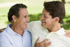Two men standing outdoors bonding and smiling Stock Photos