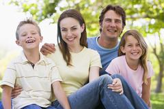 Family sitting outdoors smiling - stock photo