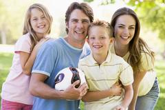 Family standing outdoors holding volleyball smiling - stock photo