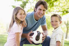 Man and two young children outdoors holding volleyball and smiling - stock photo