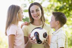 Woman and two young children outdoors holding volleyball and smiling - stock photo