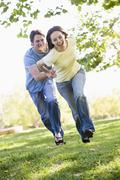 Couple running outdoors holding hands and smiling - stock photo