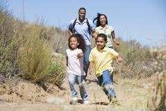 Family running on path smiling - stock photo