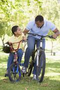 Man and young boy on bikes outdoors smiling Stock Photos