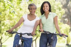 Two women on bikes outdoors smiling Stock Photos