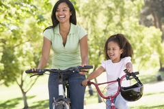 Stock Photo of Woman and young girl on bikes outdoors smiling
