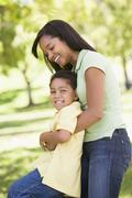 Woman and young boy outdoors embracing and smiling - stock photo