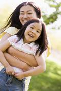 Woman and young girl outdoors embracing and smiling - stock photo