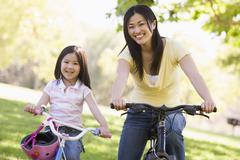 Woman and young girl on bikes outdoors smiling Stock Photos