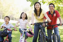 Family on bikes outdoors smiling - stock photo