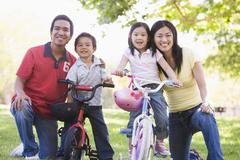Stock Photo of Family with children on bikes outdoors smiling