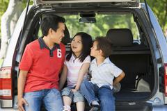 Man with two children sitting in back of van smiling - stock photo