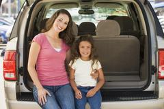 Woman with young girl sitting in back of van smiling - stock photo