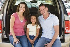 Family sitting in back of van smiling Stock Photos