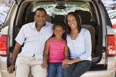 Family sitting in back of van smiling - stock photo