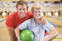 Man and young boy in bowling alley holding ball and smiling - stock photo