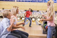 Family in bowling alley smiling - stock photo