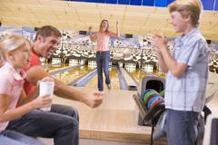 Family in bowling alley cheering and smiling - stock photo