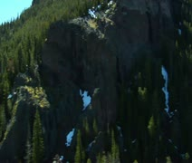 Aerial of mountain covered in pines and melting snow Stock Footage