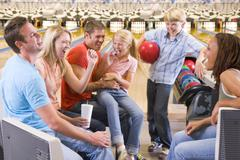Family in bowling alley with two friends cheering and smiling - stock photo