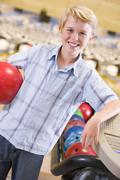 Young boy in bowling alley holding ball and smiling - stock photo