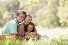 Family at park having a picnic and laughing - stock photo