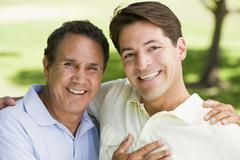 Two men outdoors embracing and smiling Stock Photos