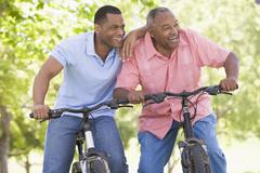 Two men on bikes outdoors smiling Stock Photos