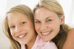Woman and young girl in living room smiling Stock Photos