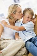 Woman kissing disgusted young boy in living room Stock Photos