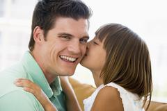 Young girl kissing smiling man in living room Stock Photos