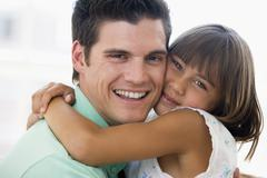Man and young girl hugging and smiling - stock photo