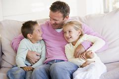 Man and two children sitting in living room smiling Stock Photos