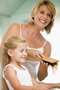 Woman in bathroom brushing young girl's hair - stock photo