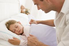 Man waking young girl in bed smiling - stock photo
