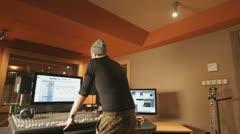 Producer explaining something in recording studio - tracking shot - stock footage