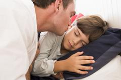 Man waking young boy in bed with kiss - stock photo