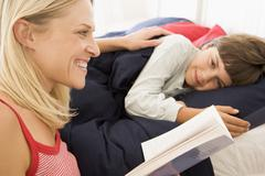 Woman reading book to young boy in bed smiling Stock Photos