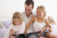 Man in bedroom with two young girls reading book and smiling Stock Photos