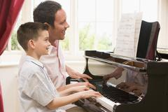 Man and young boy playing piano and smiling - stock photo