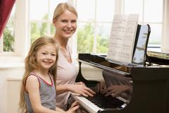 Woman and young girl playing piano and smiling Stock Photos