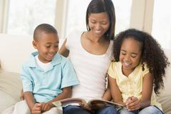 Woman and two children sitting in living room reading book and smiling Stock Photos